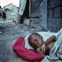 Haiti, Port-au-Prince, Malnourished girl lies on ground in Cite Soleil slum in the capital city