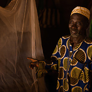 Ousseini Ouedraogo (65), with his mosquito net at his home in the village of Songodin in the Sanmatenga region of Burkina Faso on 25 February 2014. Mosquito nets greatly decrease the incidence of malaria by reducing the risk of being bitten by the nocturnal Anopheles mosquito, which carries the malaria parasite.