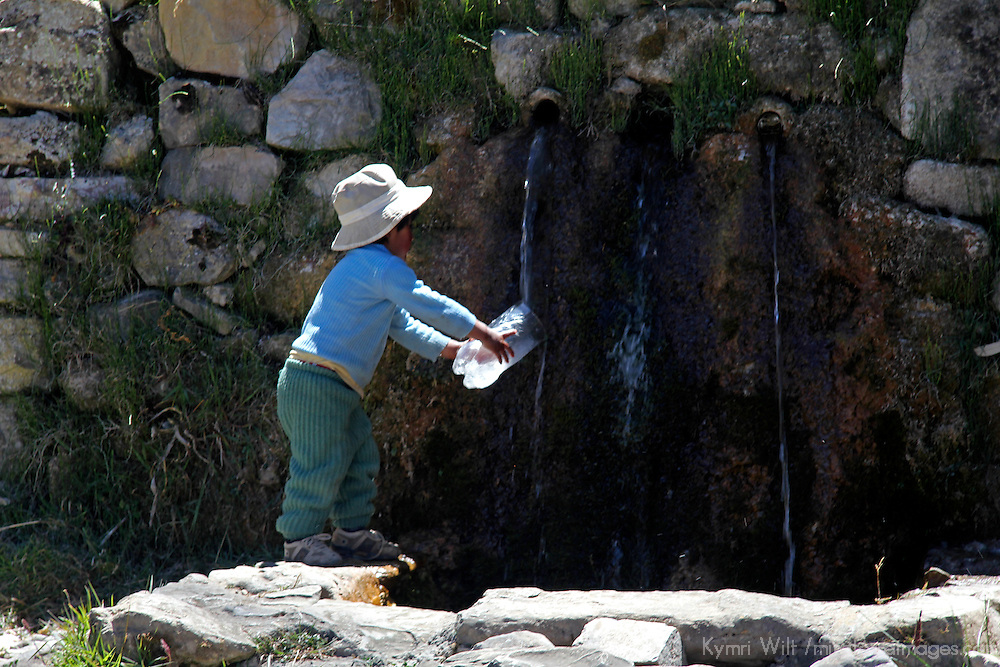 South America, Bolivia, Sun Island. Boy fills bottle at Sacred Fountain on Isla del Sol, Lake Titicaca.