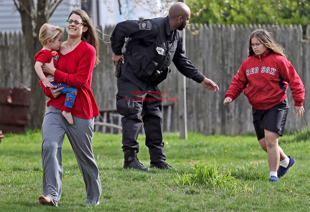 (04/19/13-Watertown,MA) A Boston police officer quickly evacuates , from left, Michelle Fehlner and her daughter Kai and Caroline Costa, age 13years, all residents of Laurel St. in Watertown, after a possible sighting of the 2nd suspect in the Boston Marathon bombing, and the killing of an M.I.T  police officer.