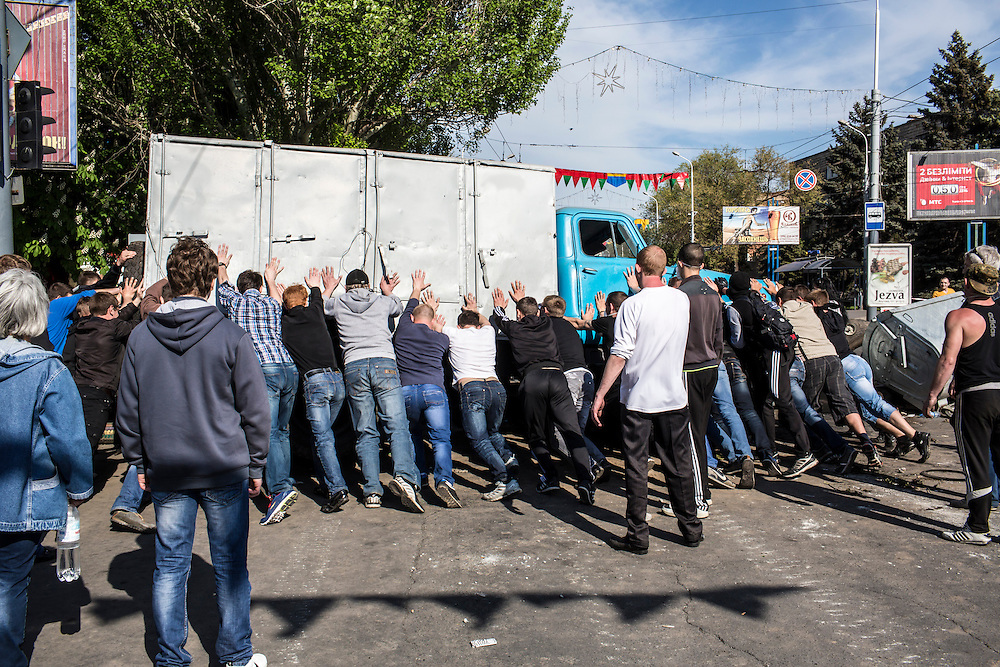 MARIUPOL, UKRAINE - MAY 11: Men try to overturn a truck at a barricade in the city center on May 11, 2014 in Mariupol, Ukraine. A referendum on greater autonomy is being held after pro-Russian activists took over at least ten cities in the eastern part of the country. (Photo by Brendan Hoffman/Getty Images) *** Local Caption ***