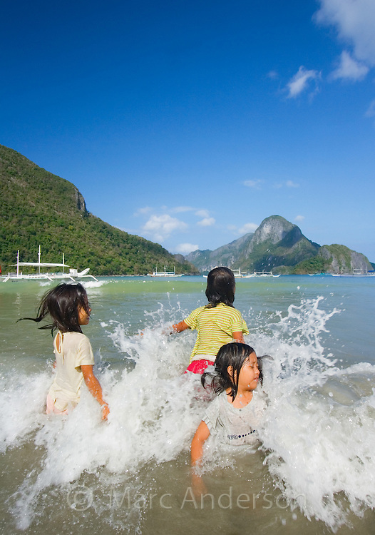 Young girls playing in the water with Cadlao Island in the background, El Nido beach, Palawan, Philippines