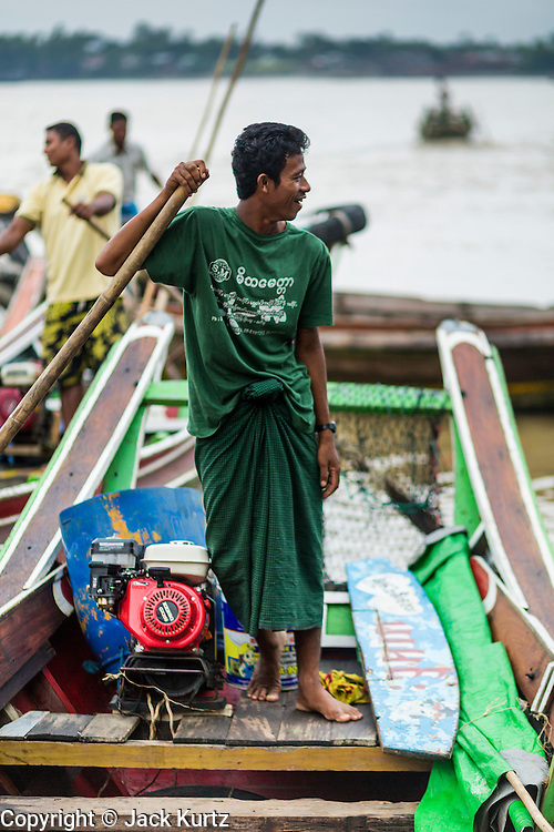 09 JUNE 2014 - YANGON, MYANMAR: A boatman waits for passengers on the Yangon side of the Yangon River near the San Pya (also spelled Sanpya) fish market. San Pya Fish Market in Yangon is one of the largest wholesale fish markets in Yangon. The market is busiest in early in the morning, from before dawn until about 10AM.    PHOTO BY JACK KURTZ