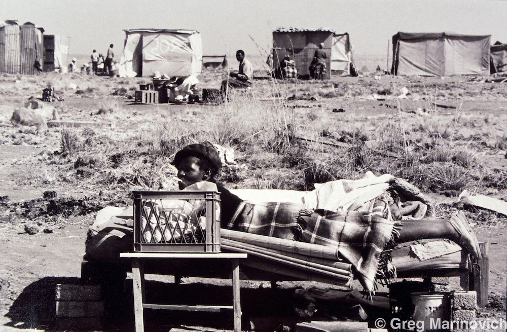Ivory Park, Thembisa, Johannesburg, Transvaal, South Africa, 1991: A woman smokes a cigarette on her bed out in the open after police demolished the shacks and shelters of people trying to squat on open land earmarked for more formal development.