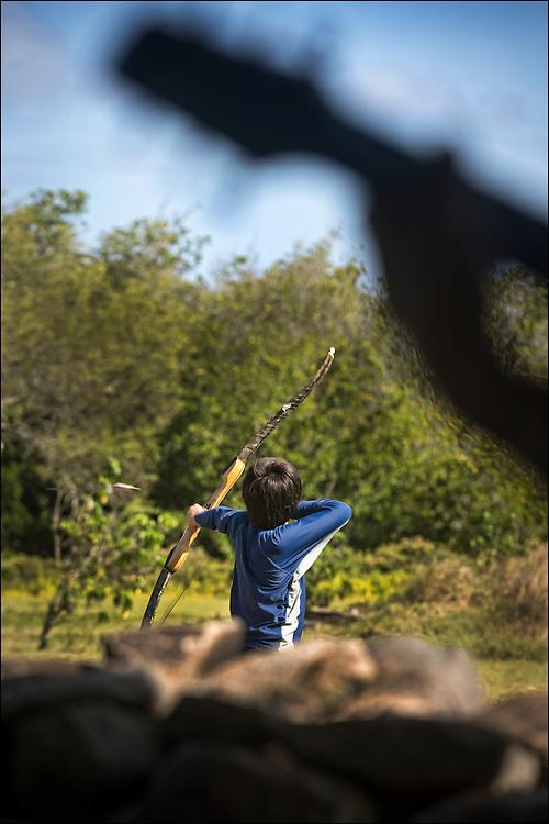 At the Keawanui Fishpond base camp, Robert Yos shoots arrow on archery skills practice while Brother Nolan plays guitar.