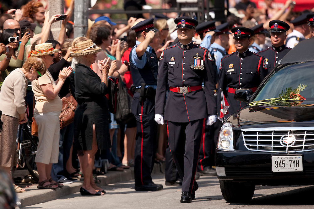 Toronto, Ontario ---11-08-27--- A large crowd applauds as the hearse with the body of Jack Layton makes its way through the streets of Toronto, Ontario, August 27, 2011 during a state funeral for the late NDP leader.<br /> AFP/GEOFF ROBINS/STR