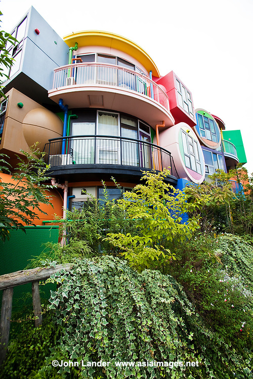 "Shusaku Arakawa designed Reverse Destiny Loft  Apartments in the Tokyo suburb of Mitaka in conjunction with his poet partner, Madeline Gins. Painted in bright colors, the building resembles a childrens playground.  Inside, apartments feature rooms with a grainy, surfaced floor that slopes erratically, electric switches are located in unexpected places on the walls so you have to feel around for the right one. One may wonder the purpose for all this, though the architect believes the apartments make you alert and awakens your instincts.  Maybe that's why their web site says the apartment  building is ""Dedicated to Helen Keller""."