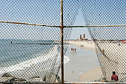 Jacob Riis Park; opened in 1932, the beach's beautiful Art Deco bathhouse has been recently restored. The beach park is separated fro Rockaway Beach with a fence, which does not stop beachwalkers from entering anyway...Rockaway Beach, Queens, New York, USA..Rockaway is making a comeback for New Yorkers who share the endless beach with the locals on weekends. Rockaway Beach is  also one of the favorite spots for surfers on the East Coast, a stretch of the beach is reserved exclusively for them. ..Deutsch: ..Der Jacob Riis Park wurde 1932 geoeffnet. Das Art Deco Badehaus wurde gerade restauriert. Der Strand Park ist durch Zaeune von Rockaway Beach getrennt. Das haelt Strandgaenger nicht vom Durchgang nicht auf...Rockaway Beach, Queens, New York, USA, Nordamerika..Rockaway erlebt eine Renaissance. Urlaubsreife New Yorker teilen sich an den Sommerwochenenden den endlosen Strand mit den Einwohnern der Halbinsel im Stadtteil Queens. Auch die Surfer zieht es hierher, es ist mittlerweile einer der beliebtesten Surfstraende der Ostkueste und die Stadt hat eigens einen Abschnitt nur fuer Surfer reserviert. Die meisten Straende sind mit der Ubahn erreichbar, auch eine neue Faehre verbindet Manhattan mit Rockaway's Jacob Riis Park in 75 Minuten.
