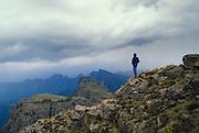 Hiker at escarpment edge, Mnweni Valley below. View looking southeast from close to Mponjwane Cave. Ukhahlamba-Drakensberg Park, KwaZulu-Natal, South Africa. Chinon CM5, 28/2.8. Fuji RD. November 1988