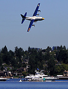 "The Blue Angels' ""Fat Albert"", a C-130T,a Lockheed-Martin Hercules four engine aircraft, flies low over Lake Washington and the log boom. An all-Marine Corps crew of three officers and five enlisted men personnel operate the plane. It carries more than 40 maintenance and support personnel, their gear and spare parts to support the Blue Angels as they travel from town to town. (Greg Gilbert / The Seattle Times)"