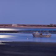 The full moon lights hte scene at Chatham Harbor.