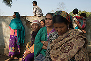 Villagers from various Rengma villages sit in the after noon sun of the Borpathar High School relief camp. In fear of continued violence the state police officers are not authorized to let the members of the relief camp leave the premises. Not accustomed to sitting around adjustment to the idle life of the camp for the notoriously hardworking Rengma-Naga has been difficult. Image © Jonah Markowitz/Falcon Photo Agency