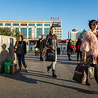 China, Beijing, Stylish young woman walks toward Beijing Central Railway Station along Second Ring Road in Dongcheng District at sunrise