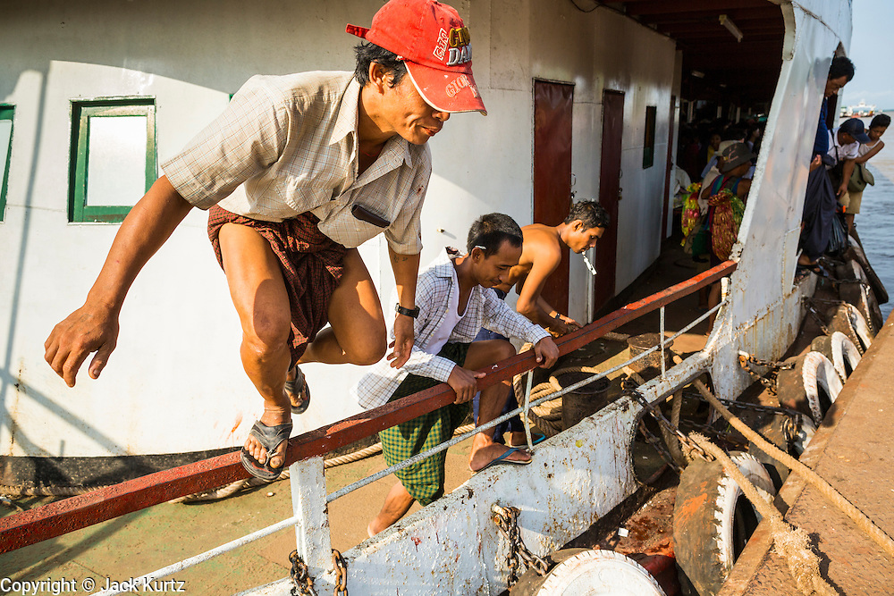 "17 JUNE 2013 - YANGON, MYANMAR: Passengers jump off the Yangon-Dala Ferry as it docks in Dala. The ferry to Dala opposite Yangon on the Yangon River is the main form of transportation across the river. Every day the ferry moves tens of thousands of people across the river. Many working class Burmese live in Dala and work in Yangon. The ferry is also popular with tourists who want to experience the ""real"" Myanmar. The rides takes about 15 minutes. Burmese pay about the equivalent of .06¢ US for a ticket.  Foreigners pay about the equivalent of about $4.50 US for the same ticket.    PHOTO BY JACK KURTZ"