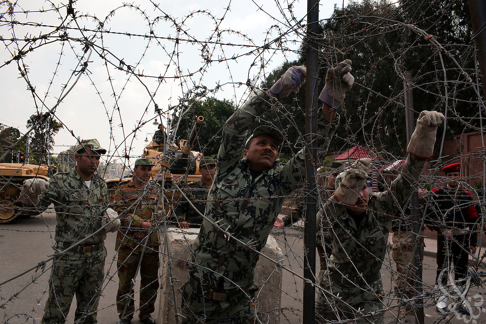 Egyptian military soldiers reinforce the barbed wire barricade outside the Orouba Presidential Palace February 11, 2011 in the Heliopolis district of Cairo, Egypt. Protesters marched Friday on a number of public buildings including the palace in an effort to spread their ongoing protests that are now in their 18th day..(Photo by Scott Nelson)