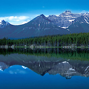 The mighty Canadian Rocky Mountains reflect in Herbert Lake in Banff National Park, Alberta, Canada.