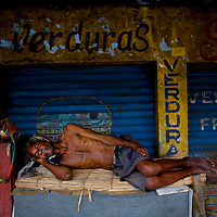 A napping worker at Basurto market near Cartagena, Colombia...Photo by Robert Caplin.