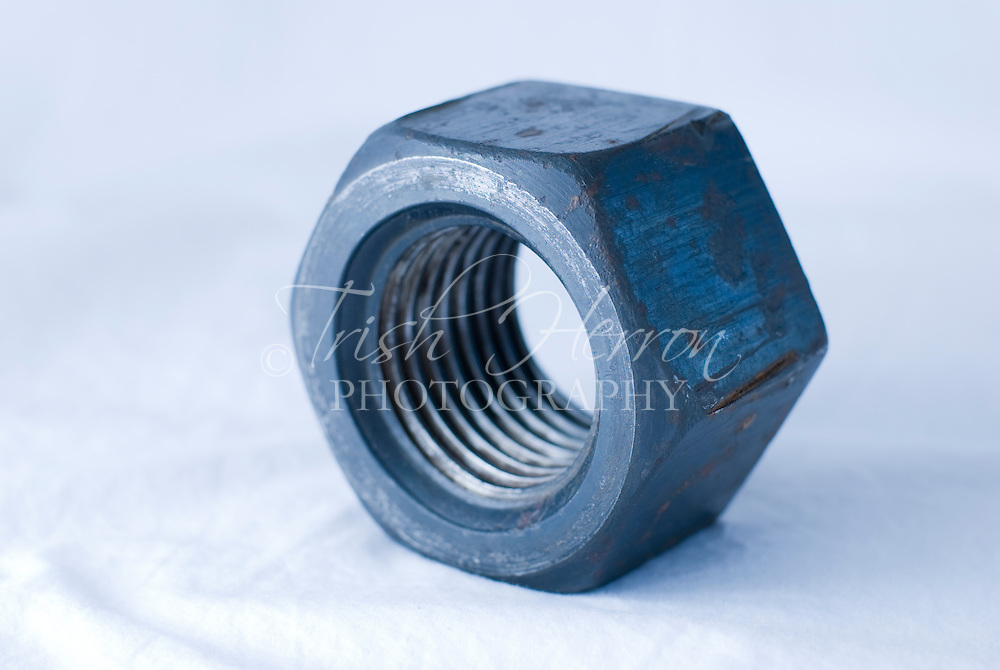 A hexagonal nut showing interior threading.