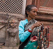 """A woman sells necklaces (some made of bone) in Kathmandu, the largest city in Nepal (700,000 people). Kathmandu is sometimes called """"Kantipur"""". The original inhabitants of the Kathmandu Valley are Newars, who speak the language Nepal Bhasa. However, Nepali is the lingua franca of the valley and is the most widely spoken language. The city stands at an elevation of 6235 feet / 2230 meters."""