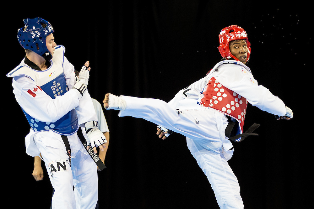 Chris Iliesco (L) of Canada tries to avoid a kick by Neyder Lozano of Colombia in their repechage contest of the men's taekwondo -80 kg division at the 2015 Pan American Games in Toronto, Canada, July 21,  2015.  AFP PHOTO/GEOFF ROBINS