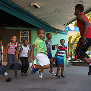Natalie Baniea leads a group of children through warm-up and fitness exercises during an afternoon boxing training session at the Hillbrow Boxing Club in Johannesburg, South Africa. Located in one of the city's most notorious neighbourhoods, the club offers a de facto after school program for neighbourhood youngsters, providing camaraderie, discipline and an activity away from the streets. Some of the children who started out this way have gone on to become national champions.