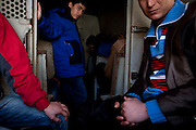 Immigrants sit in the bus waiting for instructions after having been picked up walking aimlessly in the streets of Mytilene.  Image © Angelos Giotopoulos/Falcon Photo Agency..