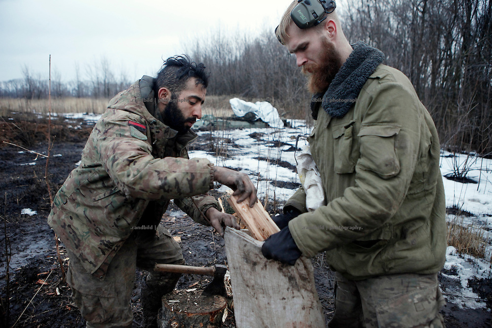 Ben (le.) and Craig fill a bag with wet fire wood for their trench position close by at the donetsk frontline.<br /> <br /> +++   +++ The Boom Stick Brotherhood +++   +++  <br /> <br /> Driven by a certain fascination on military and a simple shaped nationalistic ideology young men travel the world to fight at frontlines of recent conflicts. Five volunteering warriors from europe and the US were walking into battle in Ukraine last year. Ben, Alex, Craig, Charlie and Cowboy made it to the frontline joining the right-wing militia Right Sector (Prawji Sektor) to defend Ukraine by fighting seperatists and russian irregular forces aiming to split off the eastern Donbass region from the country.<br /> <br /> As ukrainian forces are short of servicemen Right Sector is welcomed to support the defense efforts at hotspots. Receiving no payments but shelter, food and ammonition the foreigners selfmade battlegroup Task Force Pluto found itself in a so called Anti-Terror-Operation close to the Donetsk Airport. Though Minsk II Agreement for Ceasefire is in effect several daily fire exchanges taking place between both conflict parties at the line of contact. However the war is now fought in a World War I alike stalemate in muddy trenches which were digged during the World War II.<br /> <br /> As a loose union of individuals the Boom Stick Brotherhood is no certain ukrainian phenomenon and not tied to the recent war only. If things would become boring, crazy or if the army leadership would deter foreigners from fighting Ben and his comrades would move on looking for another destination around the globe to be involved in battle. That&acute;s what they are aiming for. They are living a dream of smoking guns, camaraderie and a simple outdoor life. A lifestyle devoted to look every day into the ugly face of death.<br /> <br /> The Boom Stick Brotherhood is a multi-national, multi-religious and multi-ethnic group of men in its twenties:<br /> Ben, an austrian infantryman travelling to h