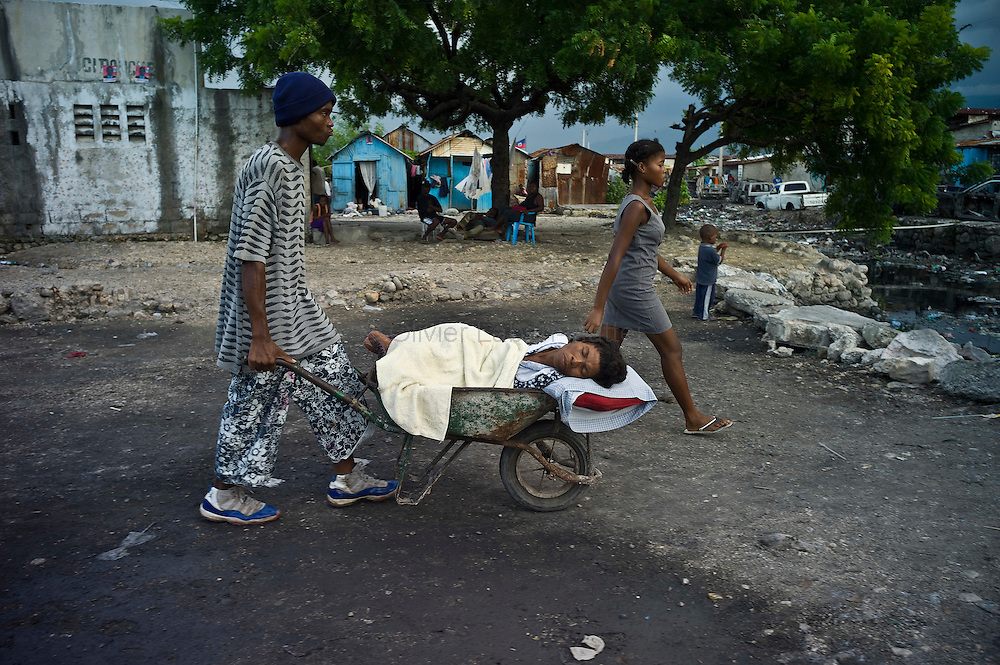 The number of cholera victims in Cité Soleil, a slum of Port-au-Prince, is increasing day by day exponentially, according to a doctor of Doctors Without Borders.///Jean-Pierre Britus and Janette Jackson carry their mother in a wheelbarrow, Kernilis St Jean, who suffered from cholera, to the nearest hospital, in the slum of Cite Soleil in Port-au-Prince.