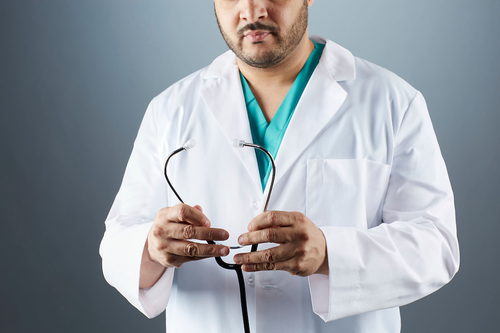 A portrait series representing the intense emotions that Doctors face.  An Afro Puerto Rican male Doctor wearing a white lab coat, stethoscope, and green medical scrub suit shown.