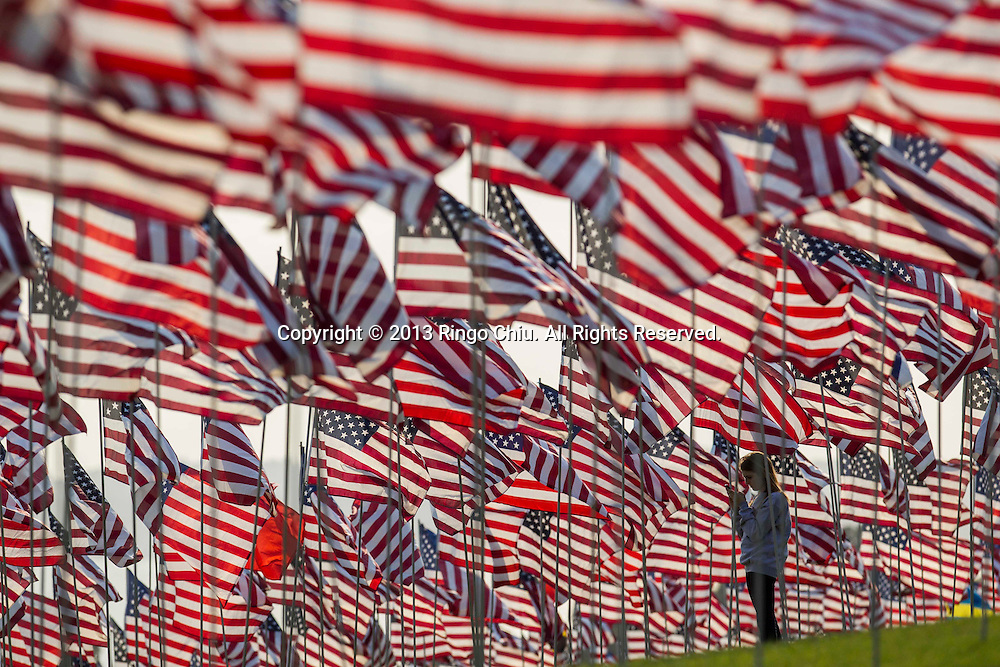 A girl takes pictures amongst 3,000 US flags are displayed at Pepperdine University to mark the 12th anniversary of the 9/11 terror attack, September 10, 2013 in Malibu, California. Photo by Ringo Chiu/PHOTOFORMULA.com)