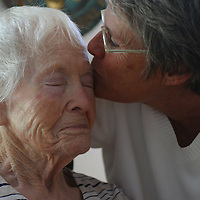 A woman with Alzheimer's disease is comforted by a healthcare worker  at  live-in residence for Alzheimer's and dementia related  patients.