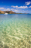 A small fishing boat on crystal clear water around a tropical around in Fiji..