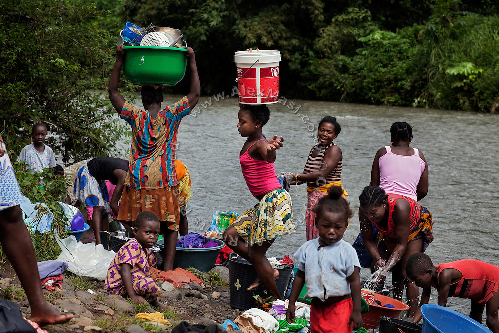 Women and youngsters are washing clothes and dishes in Ribeira Afonso, on the island of Sao Tome, Sao Tome and Principe, (STP) a former Portuguese colony in the Gulf of Guinea, West Africa.