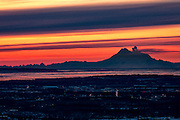 Alaska.  The city of Anchorage at sunset on a cold winter day in January with Mount Redoubt in the background on the west side of Cook Inlet.  A large column of steam is rising just below the peak of this active volcano.  Fata Morgana, an atmospheric mirage caused by a temperature inversion, is evident along the horizon, while bands of bright orange and yellow fill the sky.