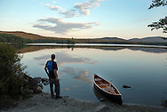 Man enjoying sunset clouds next to wood and canvas canoe at Lake Ninevah, Mount Holly, Vermont.