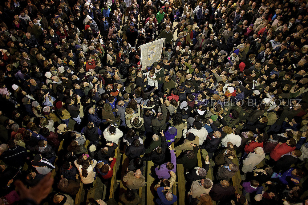 """Revelers cheers as the steward 'Paladin' carrying a banner with the image of Immaculate Conception passes by inside the church during the """"La Encamisa"""" Festival on December 7,  2014 in Torrejoncillo, Extremadura region, Spain. """"La Encamisa"""" is an ancient festival in honor of Immaculate Conception. Hundreds of horsemen wearing a white sheet gather outside the church in the main square. The procession starts when a banner with the image of Immaculate Conception is delivered to the horse rider steward 'Paladin' and people cheer and shoot blanks. There are bonfires along the way where people gather to chat, eat traditional sweets and drink local wine. The origin of this tradition is unknown but it is believed the festival comes from a military event in which people from Torrejoncillo were involved. The war in Flanders in 1585, the Battle of Pavia or a legend of the siege suffered by city of Coria. (© Pablo Blazquez)"""