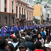 Thousands of people participate in Quito's great procession of Good Friday, which was the day when Jesus Christ was sentenced and crucified. Captured April 10, 2009 in Quito, Ecuador, Pichincha province, South America. The hooded cucuruchos and the robed Verónicas are the traditional figures who accompany Jesús del Gran Poder (Jesus Almighty) and the Virgen Dolorosa (Virgin of Sorrows) on the procession which starts and ends at the San Francisco church and passes through Quito's historic center. The cucuruchos symbolize the penitents who, dressed in purple, show their repentance and their will to change. (The traditional conical, pointed-hat robes resemble those worn in Spain and famously by the Klu-Klux Klan; Cucurucho is Spanish for cone or cornet.) Many penitents carry crosses, chain their feet, or wrap thorns around their heads. The Verónicas recall the woman who came to Jesus as he carried the cross, and who wiped his face full of sweat and blood. In Quito, the Verónicas also wear purple, their faces hidden by black shrouds.
