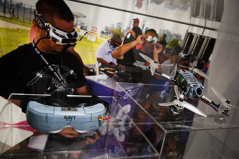 """30206010A - DRONES - A custom Navy-branded racing drone and first-person view goggles sit on display at a station talking about the new Drone Racing League at the """"Drones: Is the Sky the Limit?"""" exhibit at the Intrepid Sea, Air, and Space Museum in New York, NY on May 9, 2017."""