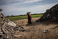 An eldery women is seen collecting wood and other material from the rubble of her district to light some fire in the near by refugee camp in Khuza's