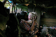 Mother tries to comfort one of her girls after she starts crying in the bedroom.  A family of two parents 12 children and 2 grandchildren struggle to survive in the forest area where living is simply existing.  The women of the family weave hats to sell at the market.  The children play with their puppies and with sticks.  They climb trees and chase the dogs.  The smile and laugh, but their existence is on the fringe.
