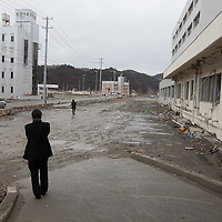 A family who lost their mother in the 2011 tsunami, and whose body has never been recovered, pay their respects outside the Minami-Sanriku Hospital, across the devastated town, on the 1 year anniversary of the March 11th 2011 earthquake and tsunami, in Minami-Sanriku, Tohoku region, Japan on Sunday 11th March 2012.