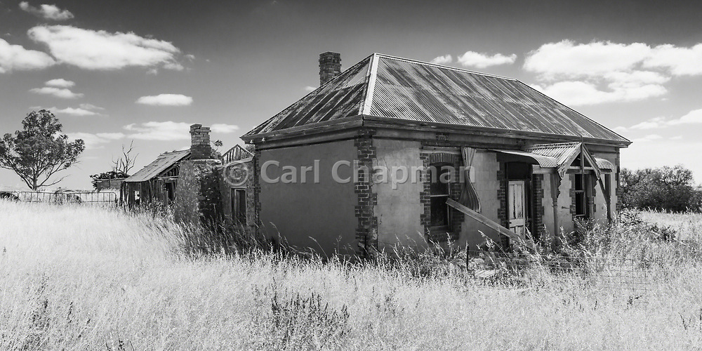 dilapidated old sandstone farm house in a field of long dry grass near Palmer, South Australia, Australia