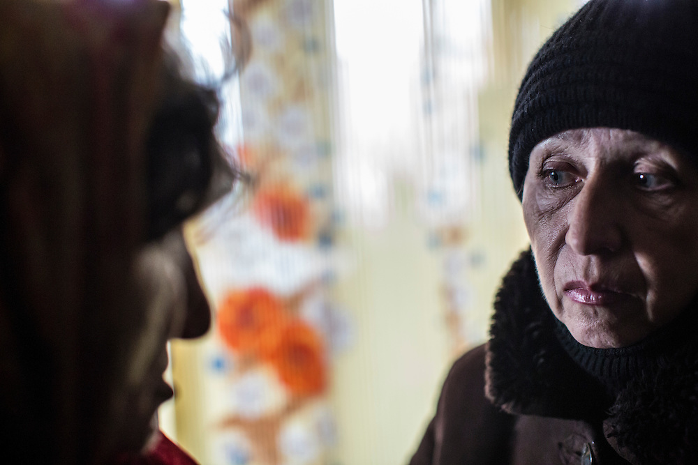 KOMUNAR, UKRAINE - JANUARY 27, 2015: Valentina Mozschagina, 80, left, is comforted by Valentina, right, a volunteer who coordinates humanitarian aide for local residents and chose not to give her last name out of fear of repercussions, in Mozschagina's home in Komunar, Ukraine. Mozschagina is the only caregiver for her disabled son Viktor, 58, and can often afford to eat only porridge. CREDIT: Brendan Hoffman for The New York Times