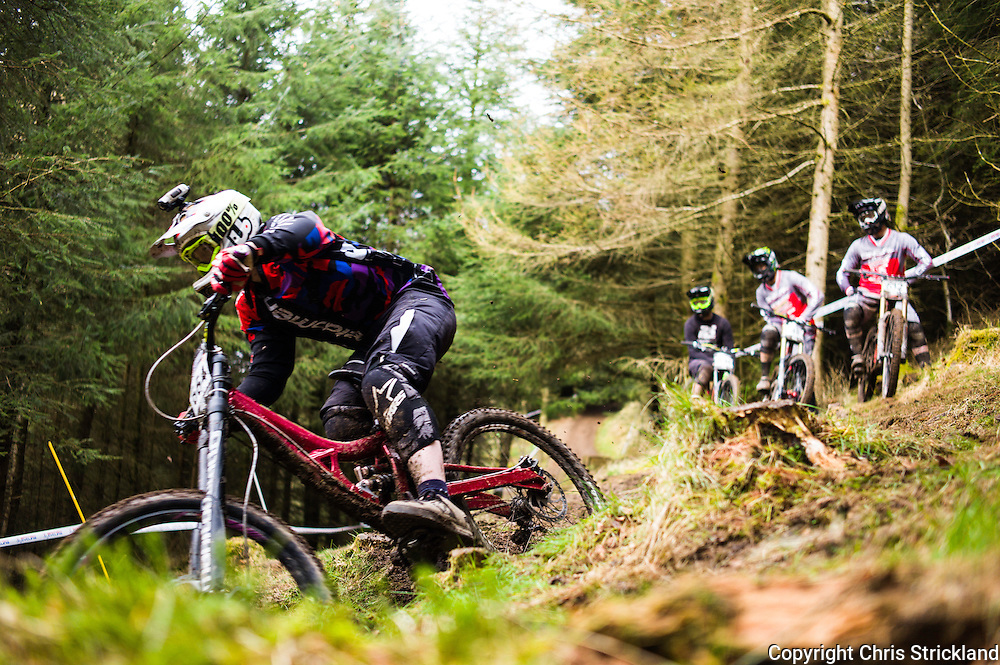 Ae Forest, Dumfries, Scotland, UK. 4th April 2015. Downhill Mountain Bikers take on the 7Stanes course at Ae during the British Downhill Series. The course length is 1.5 km starting at an altitude of 332 m and descending to 131 m. The fastest rider will aim to complete their race in around two minutes.