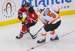 May 6, 2012; Newark, NJ, USA; New Jersey Devils left wing Zach Parise (9) and Philadelphia Flyers defenseman Braydon Coburn (5) battle for the loose puck during the third period in game four of the 2012 Eastern Conference semifinals at the Prudential Center.  The Devils defeated the Flyers 4-2.