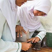 CAPTION: Students and teachers have been trained on how to use organic waste to make compost. Any excess is sold as fertiliser, and the profits generated go towards building a school garden. LOCATION: SMP N 7 School, Bandar Lampung, Indonesia. INDIVIDUAL(S) PHOTOGRAPHED: Dwi Wijayanti (left) and Putri Aryanti Fadillah (right).