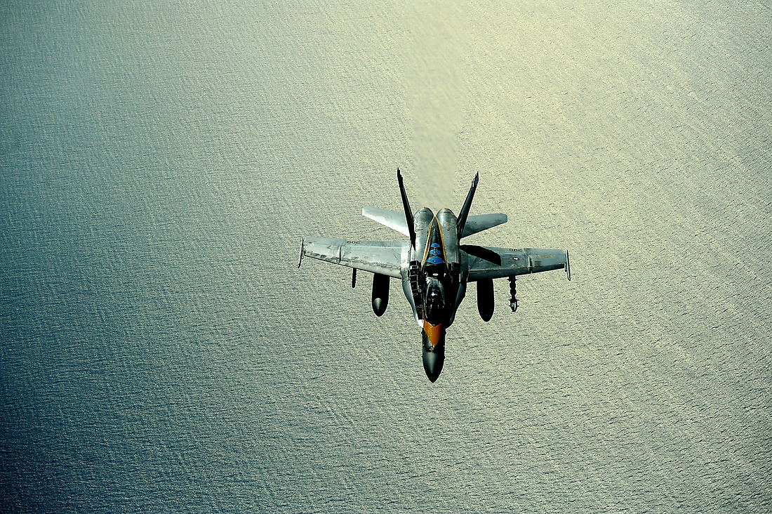A U.S. Navy F/A-18 from the U.S.S. Reagan Strike Fighter Squadron 146 (VFA-146) flies behind the tanker after receiving fuel from a KC-135 Stratotanker with the 465th Air Refueling Squadron, Tinker AFB, Oklahoma, during a refueling mission on July 8, 2010, in support of RIMPAC 2010 at Hickam AFB, Hawaii. — © MSgt Jeremy Lock/