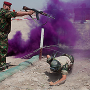 A 17th Iraqi Division officer fires blanks over the head of an Iraqi soldier as he crawls under a barb wire fence on an obstacle course during a training day event for media August 30, 2010 at the Joint Security Station (JSS) Deason in Mahmoudiyah, Iraq.