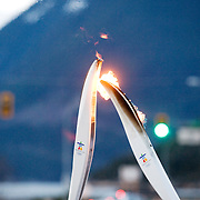 The Olympic flame is transfered from one runner to another.  Britannia Beach
