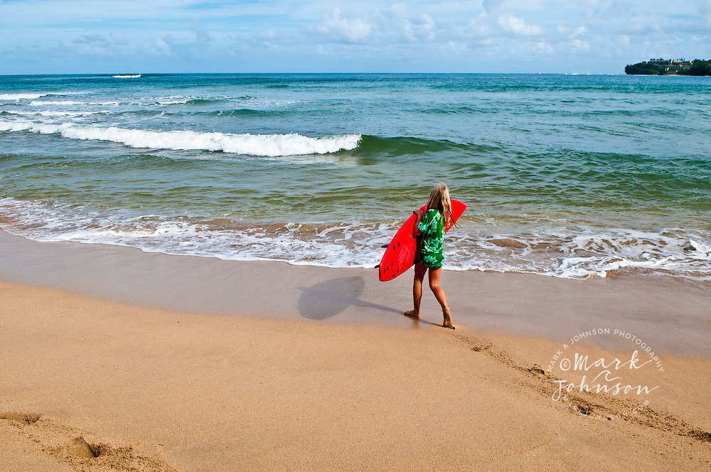 7 year old girl carrying her surfboard at Hanalei Bay, Kauai, Hawaii